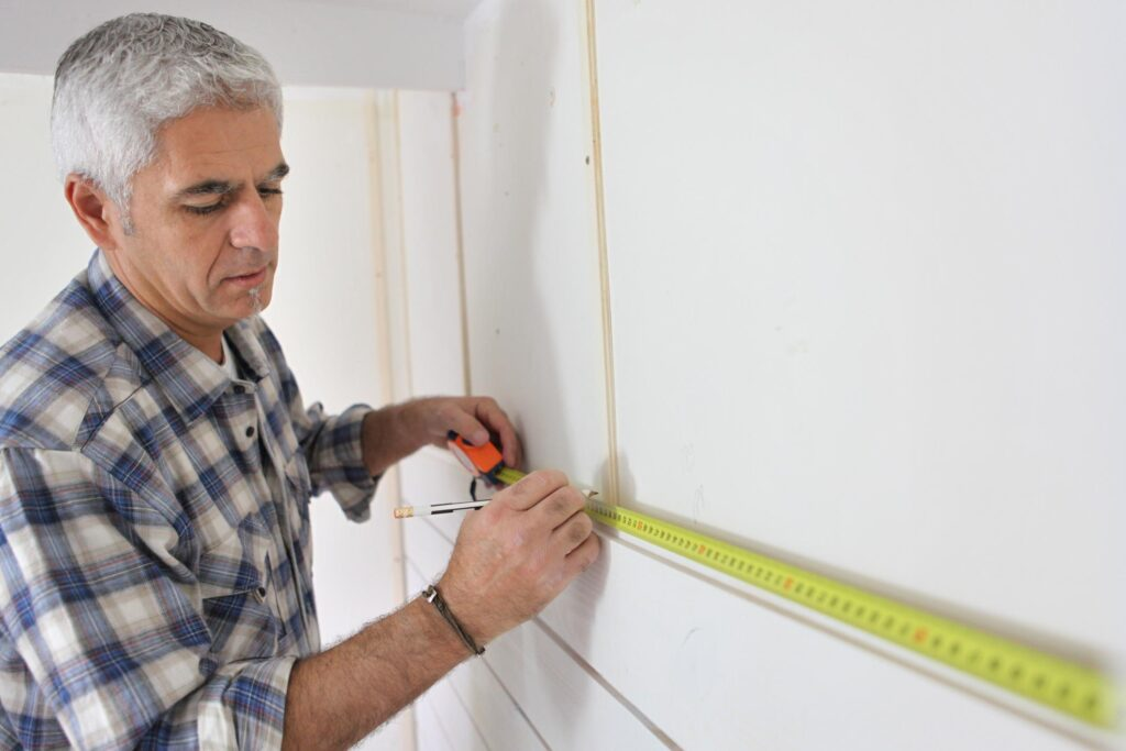 man measuring the wall